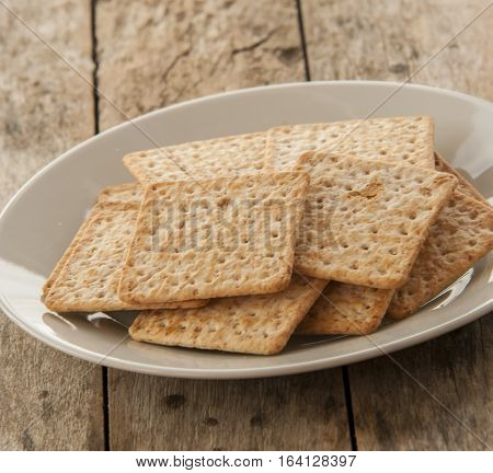 Cracker close up on white plate in wooden background