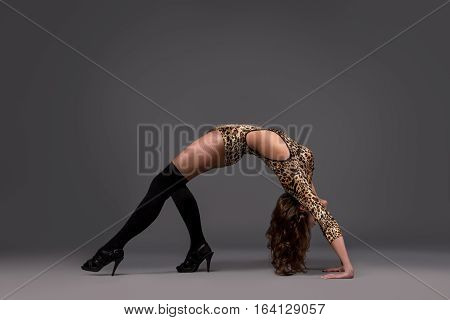 Sexy woman dancer wearing bright leotard and high heels performing at studio on dark  background
