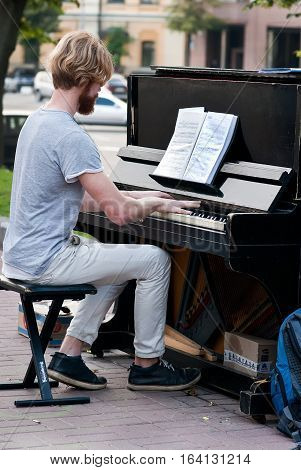 Kyiv Ukraine - June 15 2016: Unidentified man plays on a piano on Mikhailovskaya Square in the center of Kyiv. Part of the beautification program is 'Pianos About Town' where a number of pianos are placed around the downtown for people to enjoy.