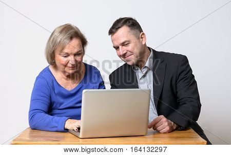 Cheerful cute senior woman in blue shirt using computer beside smiling businessman using laptop computer
