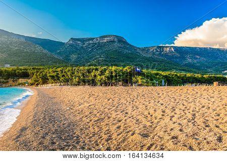Scenic view at famous Golden Cape beach (Zlatni Rat) near town Bol, Island Brac, with highest island peak VIdova Gora in background, Croatia european touristic destination.