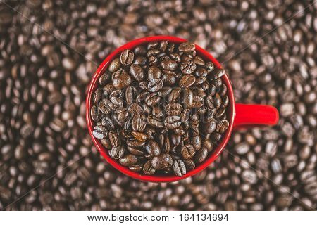 Coffee beans in red cup mug macro close up detailed well roasted in vivid colors overhead shot. Concept for freshness morning cozy lifestyle.
