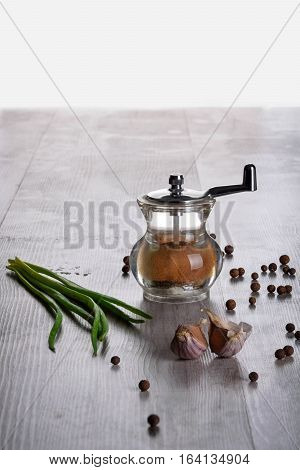 pepper mill young onion garlic cloves and pepper peas on a wooden background
