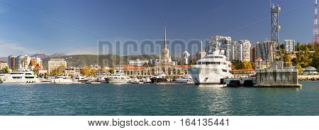 Sochi Russia - November 1 2015: View from water at Sochi sea port. Luxury yachts and private boats moored at pier. In background architecture modern resort town hotels and sanatoriums. Marine station complex Port. Krasnodarskiy kray Russia