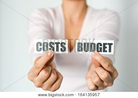 Budget planning concept with woman hands holding two printout with cost and budget words