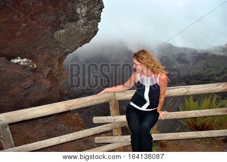 The young beautiful girl at a muzzle of a volcano of Vesuvius.