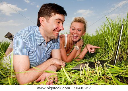 Casual happy couple are talking  and laughing on a laptop computer outdoors. Lay on the green grass.