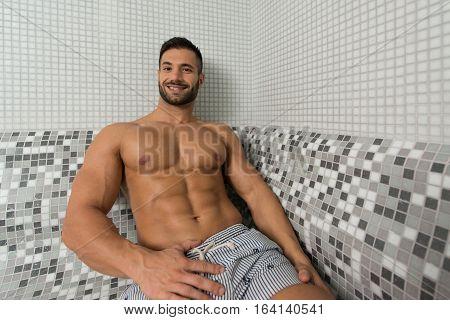 Portrait Of A Muscular Man Relaxing In Sauna