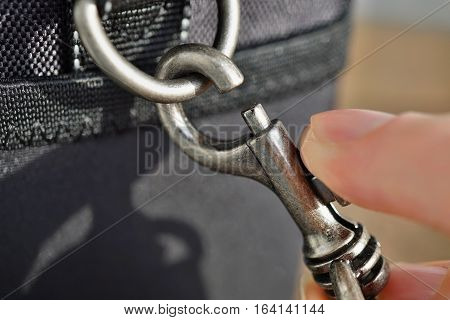 Macro detail of male finger releasing a snap-hook (snap-link) fastened to the black bag with silver loop as a symbol of safety link between two objects