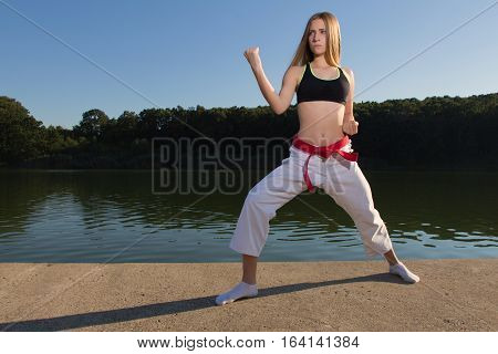 Karate girl practicing zenkutsu dachi soto uke kata on lake near the water