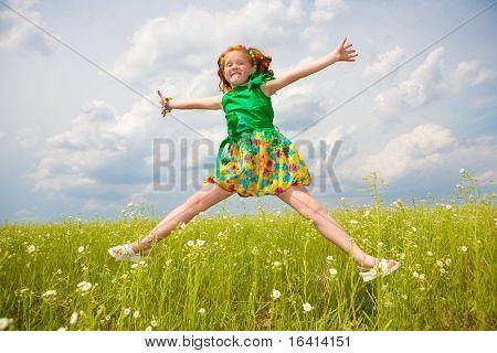 Klein meisje springen tegen mooie hemel