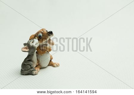 Toy of a dog with a cat on a light background