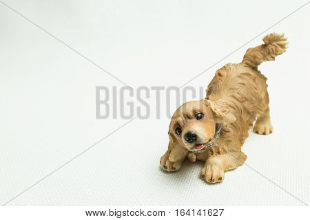Toy of a dog sat down on forepaws on a light background