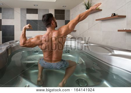 Guy Flexing Muscles In Azure Jacuzzi