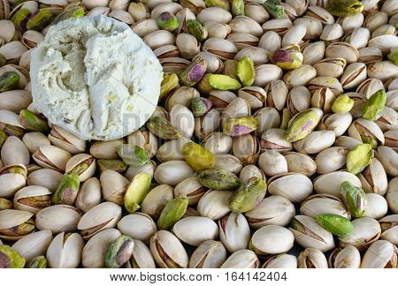 One scoop of Pistachio Ice Cream on Pistachios with lots of copy space. Selective focus on ice cream scoop.