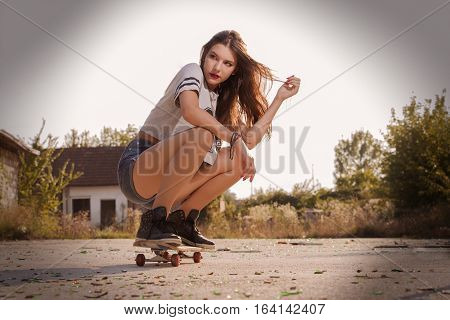 Tenage girl crouched on skateboard. Outdoor urban scene,