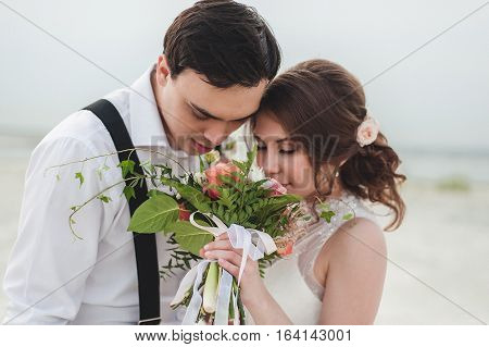 Beautiful bride and groom smell the scent of a bouquet of flowers