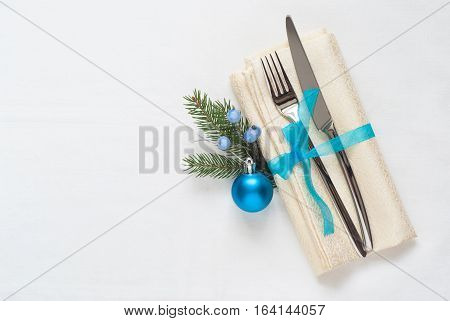 Christmas silverware at white tablecloth blue decorations. Top view copy space.