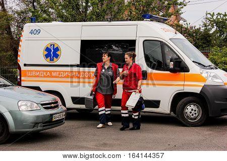 KIEV REGION, UKRAINE - May 12, 2016: ambulance and a nurse on the street. Ambulance is near the hospital