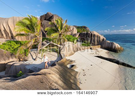 Female traveler emjoying climbing ob beautifully shaped granite boulders at picture perfect tropical Anse Source d'Argent beach, La Digue island, Seychelles.