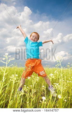 Happy boy jump in the field