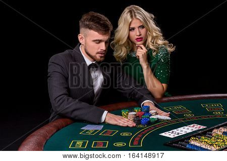 View of young, confident, man with the lady while he's playing poker game. Man bets in poker