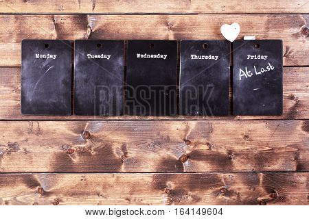 Weekday blackboard notices with a message on Friday saying 'At Last' the week has ended. Rustic wooden background poster