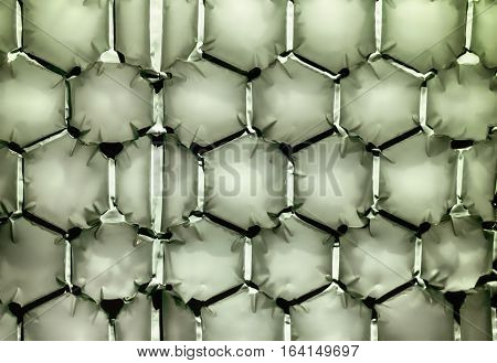 Hexagonal bubble texture background in light green showing shadows and relief.