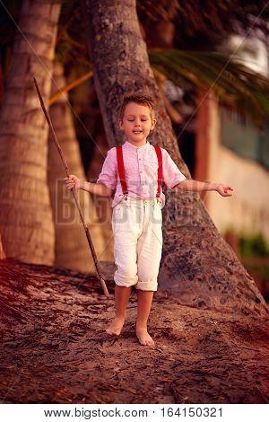 Stylish Cute Boy Exploring Tropical Palm Grove