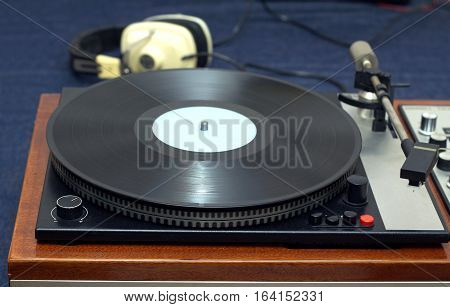 Vintage analogue classic style record player in wooden case with vinyl record with blue label and headphones. Horizontal photo front view closeup