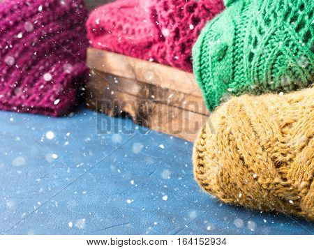 Winter womans woolen sweaters. Knitted girls clothing. Colorful pullovers on wooden background. Cozy clothes for the season. Copy space