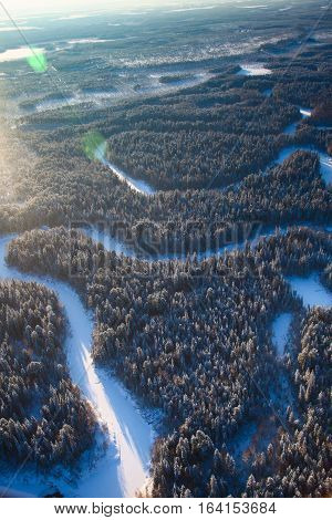 Aerial view of coniferous forest with small river during a winter day.