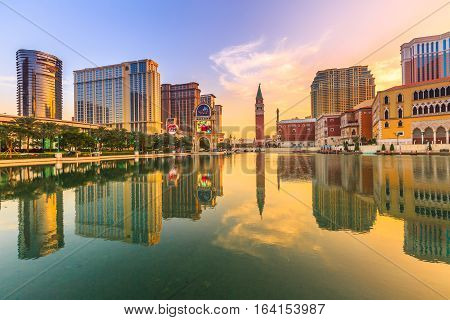 Macau, China - December 9, 2016: Luxury resort Casino in Cotai Strip, The venetian Mall and Tower, Hard Rock, St Regis, Holiday Inn, Conrad, Sheraton, reflecting on artificial lake at dusk.