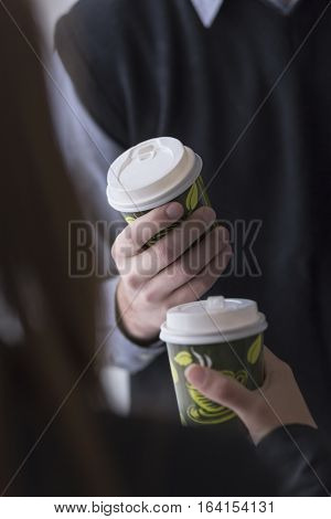 Detail of a two business colleagues on a coffee break holding a coffee to go cups