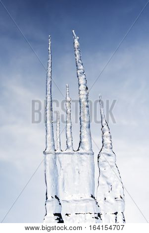 large icicles forming with blue sky backdrop
