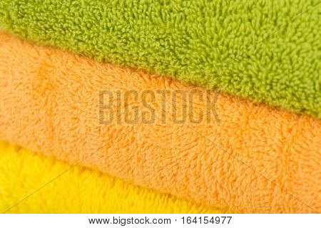 Stack of beautiful colored bath towels in a green, blue, yellow color. Close up. Everyday care about your body. Everything for your hygiene. Pile of nice fluffy and soft towels. Domestic objects