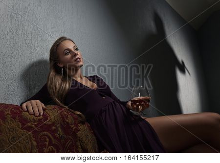 Young beautiful woman in evening dress and the culprit's shadow on the wall