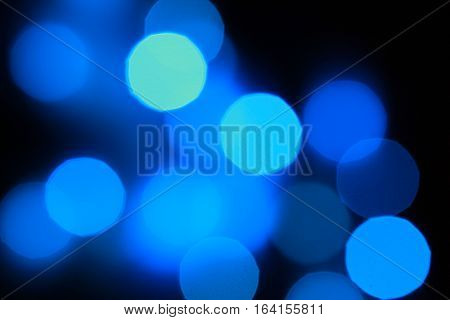 Twinkling blue lights bokeh with black background.