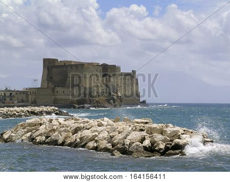 Napoli, Italy. Castel dell'Ovo, photographed from Via Caracciolo, with waves breaking on the rocks.