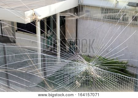 Broken shuttered glass window panel with view of building behind.