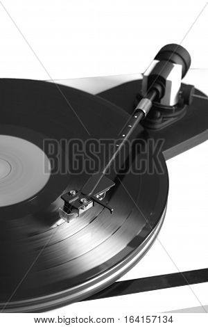 Vintage turntable in silver case playing vinyl record with red label . Vertical black and white photo isolated on white background closeup
