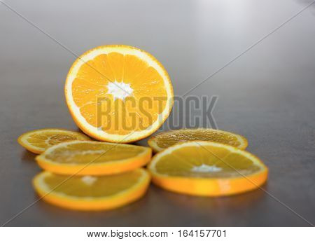deliciously sweet ripe orange cut into slices laid on a shiny bar board