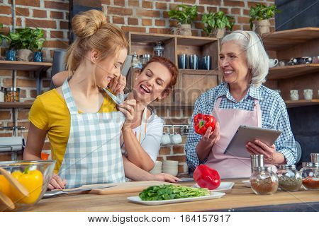 Smiling family of three cooking together in kitchen