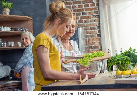 Happy family cooking together vegetable salad in kitchen