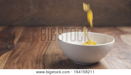 motion blurred corn flakes falling into white bowl on wooden table, simple photo with copy space