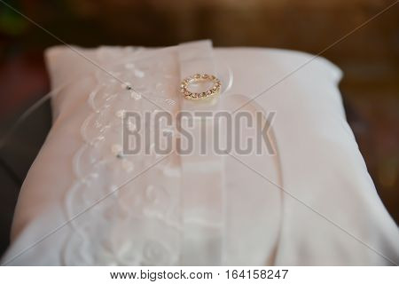 Wedding ceremony accessories. Golden rings on white pillow