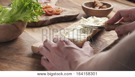 man spread cream cheese with herbs over baguette in slow motion, 4k photo