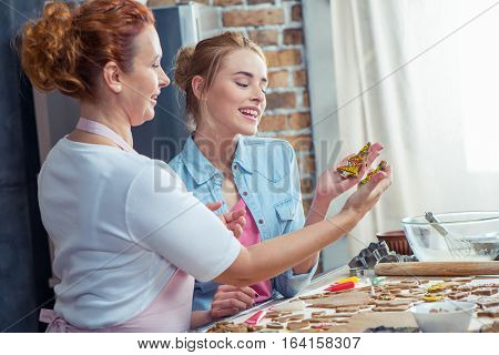 Mother and daughter making Christmas cookies in kitchen