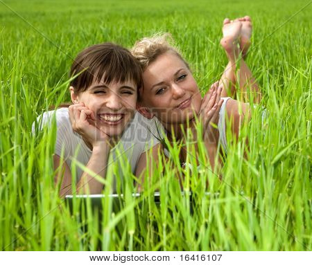 Two beautiful girls in white clothes are laughing at laptop computer outdoors. Lay on the green grass.