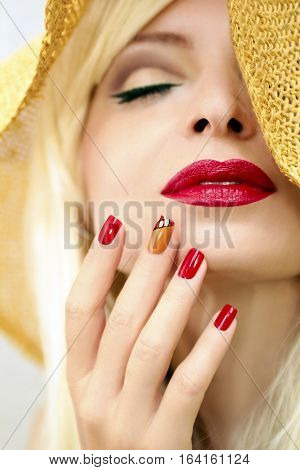 Red straw nail design girl model with red lips and a straw hat on his head.